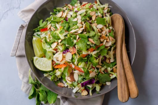 Crunchy Asian Cabbage Slaw with a sweet, gingery and slightly spicy peanut sauce. This will be your new favorite crunchy salad!
